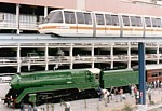 Monorail train passing above steam locomotive 3801 stopped with passenger train thumbnail